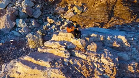 балканский : Aerial, lonely young man playing guitar sitting on a coastal rock Стоковые видеозаписи