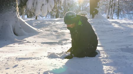 kardan adam : Young man making a snowball on a sunny winter day Stok Video
