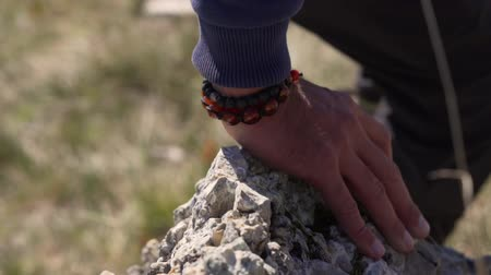 koordination : The man runs and jumps over the stone. Close-up of a hand on a stone