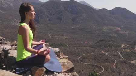 Young athletic woman meditating on the top of a mountain, zen yoga meditation practice in nature Vidéos Libres De Droits