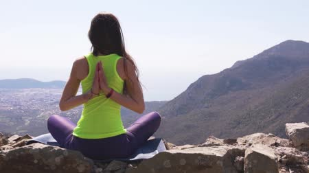 Young athletic woman meditating on the top of a mountain, zen yoga meditation practice in nature Filmati Stock