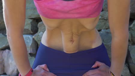 close-up of woman practicing the movement of the abdomen nauli yoga technique.