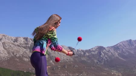 Woman spinning poi on the top of the mountain.