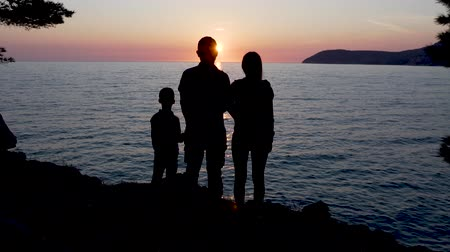 Silhouettes of a young family standing near the sea at sunset.