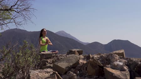 Young athletic woman meditating on the top of a mountain, zen yoga meditation practice in nature Stockvideo