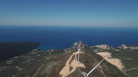 Aerial view of windmills against the sea, laid out on the mountain.