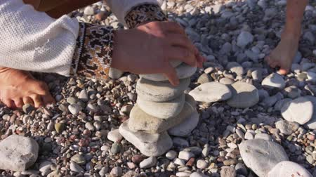 kırılganlık : Close-up family, hand folds a pyramid of stones on the seashore.