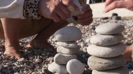 fragilidade : Close-up family, hand folds a pyramid of stones on the seashore.