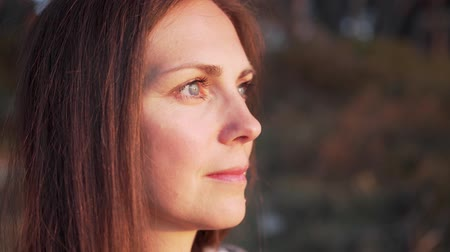 Close up of womans face at sunset, beautiful green eyes, portrait, outdoor relax sunlight. 動画素材