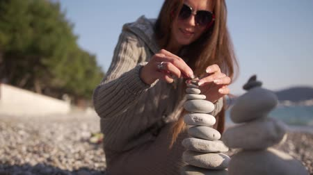 fragilidade : Close-up girl, hand folds a pyramid of stones on the seashore.