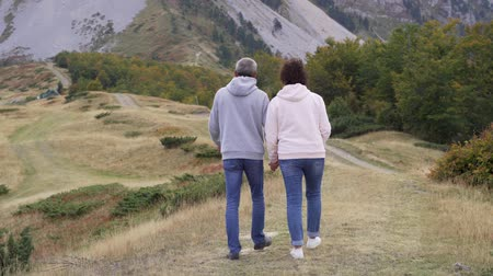 Active senior couple hiking in mountains, enjoying their adventure.