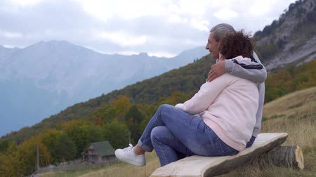 yaşlılar : Elderly travelers on a wooden bench hugging and enjoying the mountain view.