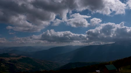 montanhas rochosas : Time lapse of clouds flowing across the blue sky over the tops of the mountains.