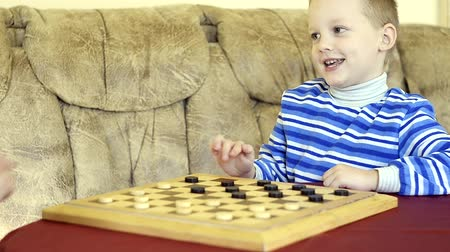 estratégico : little boy plays checkers with his grandmother Stock Footage