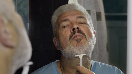 борода : Elderly man shaving and performing various grooming activities to the face Стоковые видеозаписи