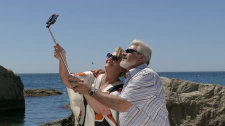 novato : Mature Couple Taking Selfie On Smartphone At Beach Resort First Time Stock Footage