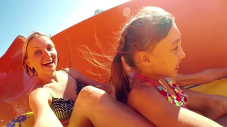 slayt : Happy woman with her daughter sliding down the waterslide in a waterpark