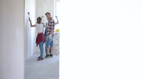 drabina : Father, mother and daughter painting wall in apartment room. Beautiful young family doing repairs in new flat. Parents and teen girl making decorate room, laughing and having fun.