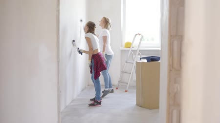 щеткой : Mother and daughter painting wall in apartment room. Beautiful family doing repairs in new flat. Woman and teen girl making decorate room, laughing and having fun.