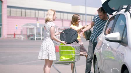 troli : Happy family with shopping cart with purchases in parking lot near supermarket. People putting bags with food into car trunk and sits in car. Mom, Dad, Children having fun outdoors near grocery store.