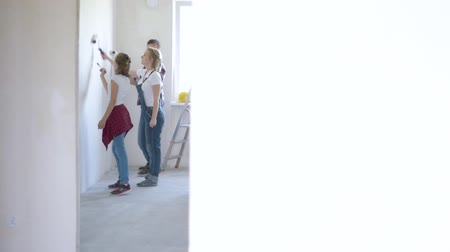 drabina : Father, mother and daughter painting wall in apartment room. Beautiful young family doing repairs in new flat. Parents and teen girl making room Wideo