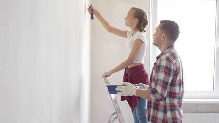 drabina : Painting wall in apartment room. Dad and daughter spend time together, doing repairs. Girlfriend on the wall of her father.