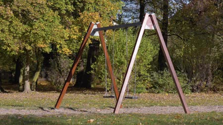 donuk : Abandoned empty swings swaying in the wind at children playground outdoors -  in a park an autumn sunny day.