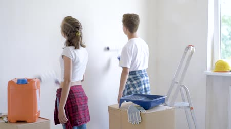 brothers : Teen boy and girl makes repairs in new flat. Sister and brother painting wall in apartment room. Children paints the wall, using a rollers. Young friends laughing and having fun.
