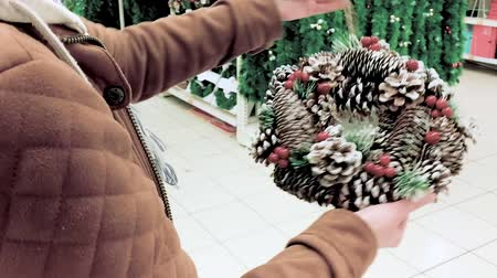 seçme : Attractive girl at the store chooses Christmas wreath. Black Friday or holidays concept. Young woman buyer found a Xmas decor - toys and tinsel for New Year at market. Stok Video