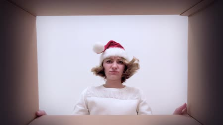 paket : Young happy woman with Christmas hat opening cardboard box and looking upset. Girl unboxing gift - different versions of emotions. Concept of holidays and New Year. POV of female looks in box.