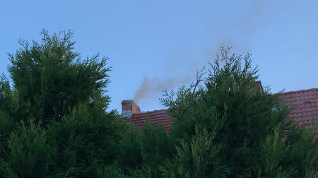 baca : Smoke comes from the chimney of the country house against the blue sky.