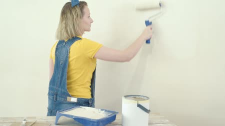 obnova : Young female makes repairs in new flat. Beautiful woman - painting wall in apartment. Woman doing overhaul of house. Girl making decorate room, smiling and having fun. Dostupné videozáznamy