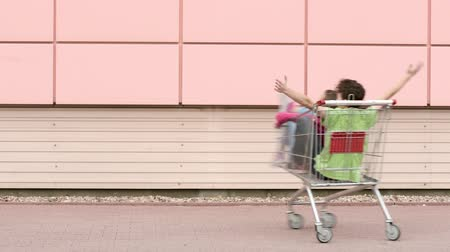 駐車中 : Happy teen boy and girl is riding in shopping carts in a parking lot near a supermarket. Young friends children having fun outdoors with shopping trolleys race.