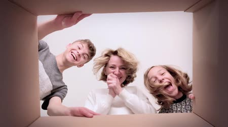 odlišný : Happy family - mom, son and daughter opening present cardboard box and looking inside. Woman and children unboxing gift - different emotions. Concept of holidays Christmas, Birthday or New Year