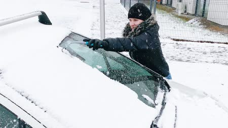 scraper : Young Woman Cleaning Car from Snow and Ice. Female removing cleaning snow from Parked Car. Snowing Storm Car Covered Winter Cold Day