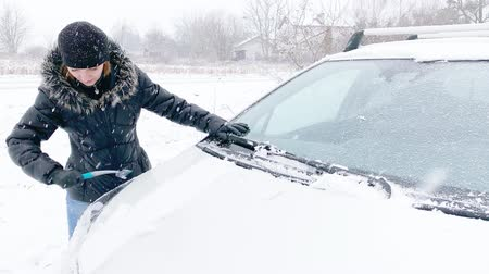 スクレーパー : Young Woman Cleaning Car from Snow and Ice. Female removing cleaning snow from Parked Car. Snowing Storm Car Covered Winter Cold Day