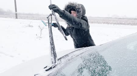 mrazivý : Young Woman Cleaning Car from Snow and Ice. Female removing cleaning snow from Parked Car. Snowing Storm Car Covered Winter Cold Day
