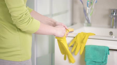 lavatório : Female hands in yellow rubber gloves Woman doing chores in the bathroom. Housework, housekeeping, cleaning and people concept.