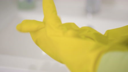 servant : Female hands in yellow rubber gloves Woman doing chores in the bathroom. Housework, housekeeping, cleaning and people concept.