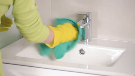 housekeeper : Female hands in yellow rubber gloves Woman with rag doing chores in the bathroom. Housework cleaning concept.
