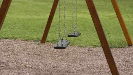 Empty playground after rain. Swing got wet in raindrops. Summer or spring rainy day. No people. No children.