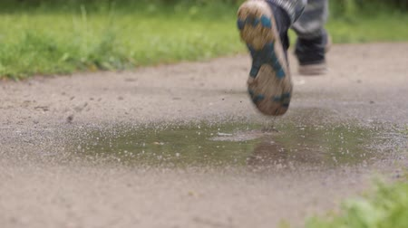 Close-up slow motion shot of male legs runner in old sneakers. Man  running in rain, stepping into muddy puddle and making splash.