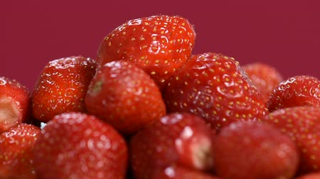 Fresh red Strawberries rotate, closeup video. Many juicy ripe berries strawberries on red background. Dostupné videozáznamy