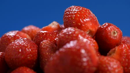 Fresh red Strawberries rotate, closeup video. Many juicy ripe berries strawberries on blue background.
