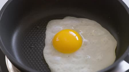 Human hands puts egg on frying pan. Egg being dropped on hot pan. Broken Chicken egg falls into the frying pan. Cooking egg on fry pan. Top view close-up.