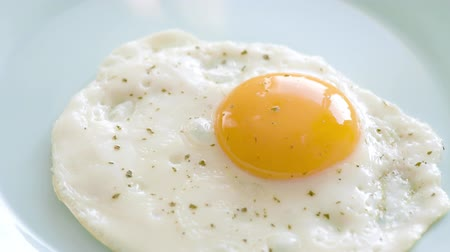 Fried egg with spices are laid out from frying pan on plate. Top view close-up.