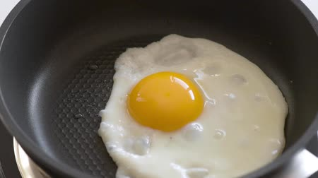 omlet : Egg fried on hot Pan. Cooking Chicken egg on fry pan. Top view close-up. Stok Video