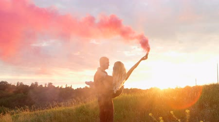 hipster : Happy couple walking through the field with smoke bombs on the background of sunset Stock Footage