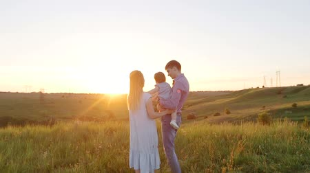 miłość : Young happy family with baby. They go to the picturesque green field at sunset. Wideo