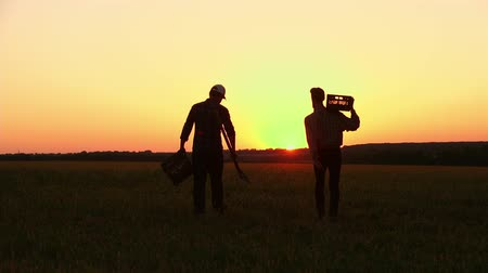 лопата : two farmers with a shovel walking on the field. They carry equipment for planting a tree. On the Sunset. Side view